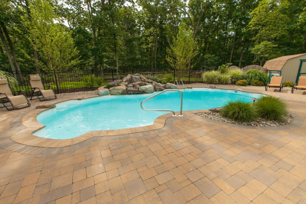 Custom inground pool in the backyard of home during the day, with trees in the background.
