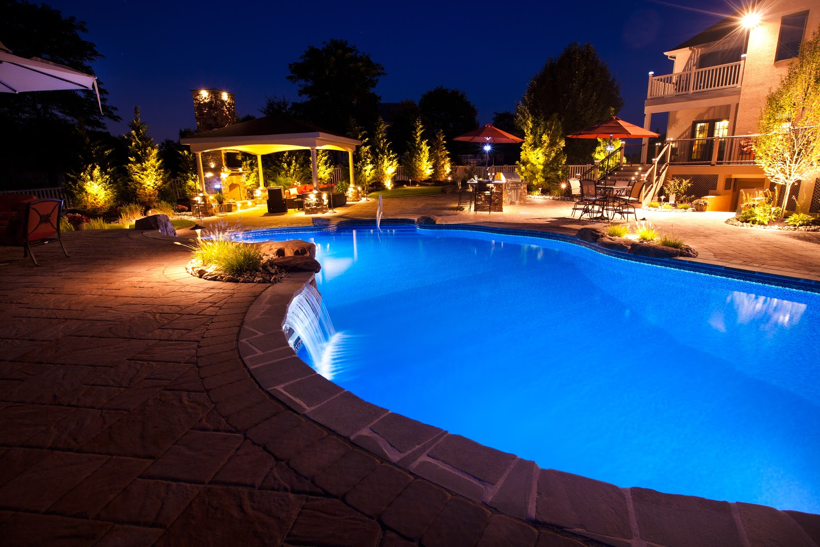 Home backyard at night featuring a custom inground pool and other outdoor living elements.