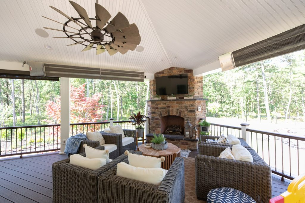 Detailed look at covered patio, showcasing chairs, tv, fireplace, and overhead heaters.