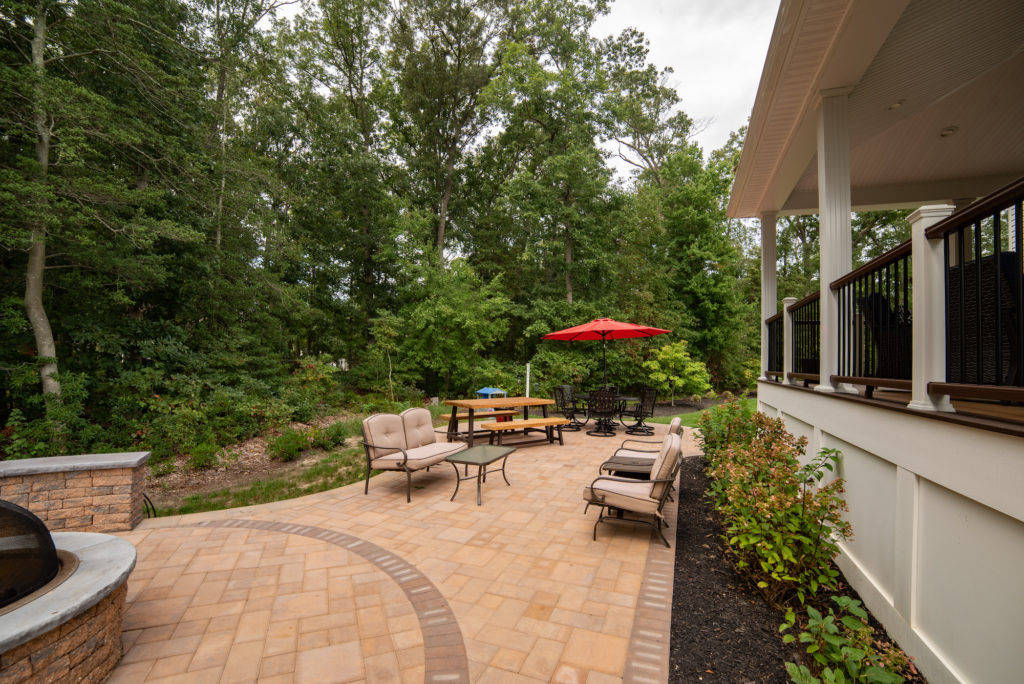 A brick patio with outdoor furniture and firepit features a dynamic design, flanked with lush green trees and landscaping.