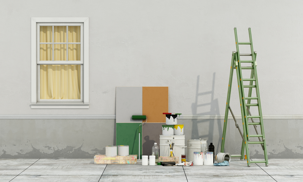 A paint palette with four colors is positioned against the outside of a grey house, with a green ladder ready to use.