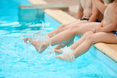 Three children sitting on edge of pool kicking feet in the water.