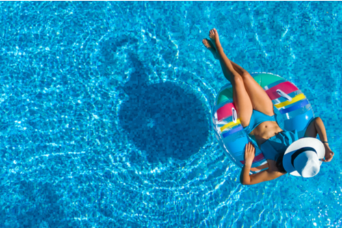 Aerial view of a slender woman wearing a white hat lying on an inner tube in the pool.