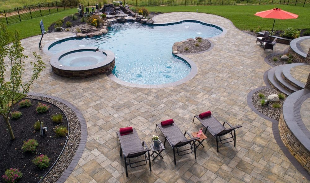 Aerial view of custom, in-ground pool featuring built-in jacuzzi, a waterfall, and 3 lounge chairs.