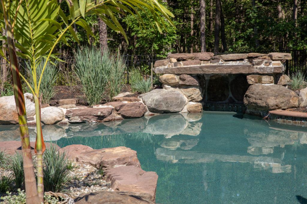 A rocky gunite pool with a grotto opening in a natural setting.