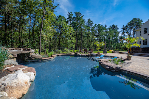 Custom-built, in-ground pool with rock formations and a curved platform.