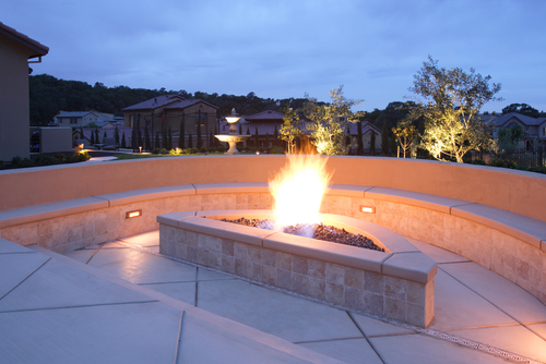 Triangle-shaped, lit concrete fire pit surrounded by concrete bench in home backyard.