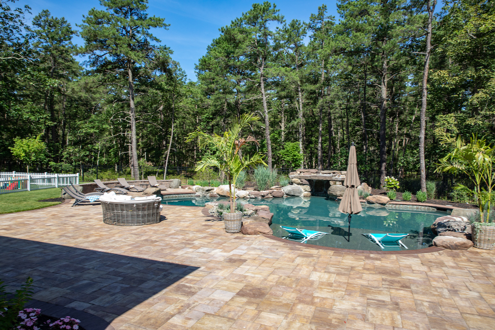 Custom-built in-ground pool in backyard, featuring an in-pool shallow platform with an umbrella and a rock cave.