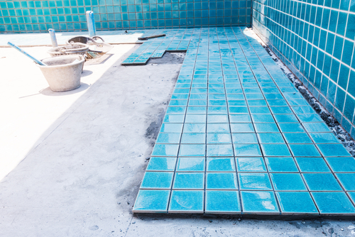 Blue tiling in the process of being installed on the floor of an in-ground pool.