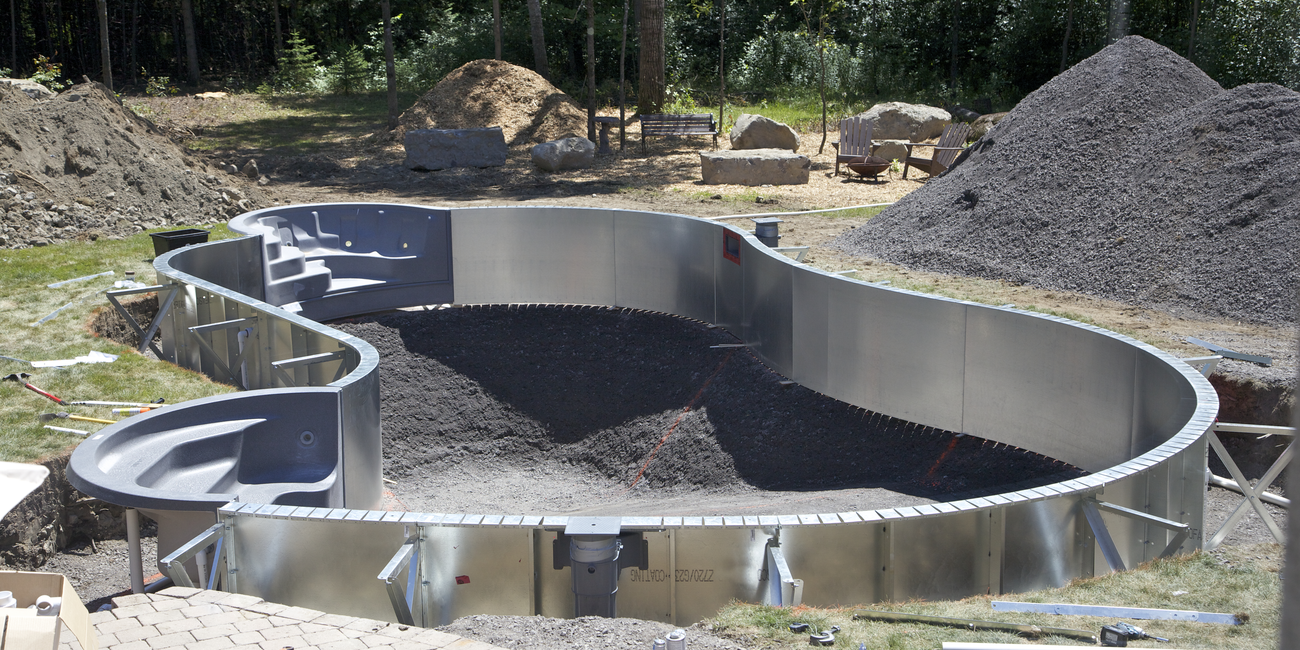 Shell of in-ground pool being built with large piles of dirt surrounding it.