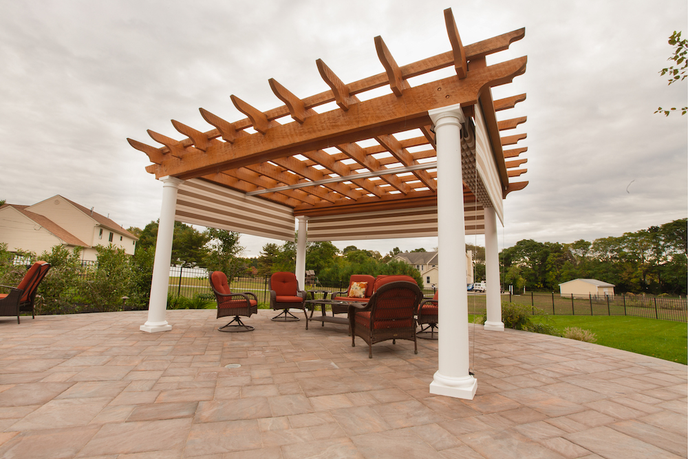 Brown pergola on brick floor in backyard, with 2 red chairs underneath.