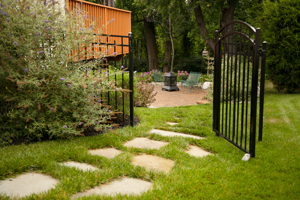 Flagstone path leading to backyard, black fence gate opened.