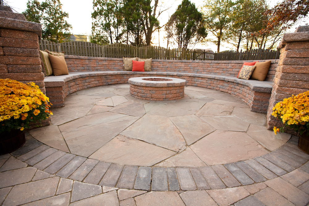 Brick floor leading to brick fire pit and long, concrete bench in backyard.