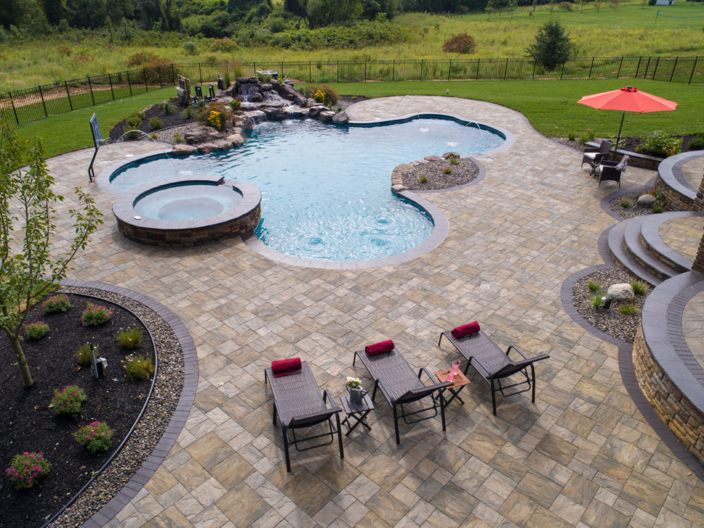 Freeform pool featuring a waterfall and inbuilt spa, with a stone patio and three lounge chairs.