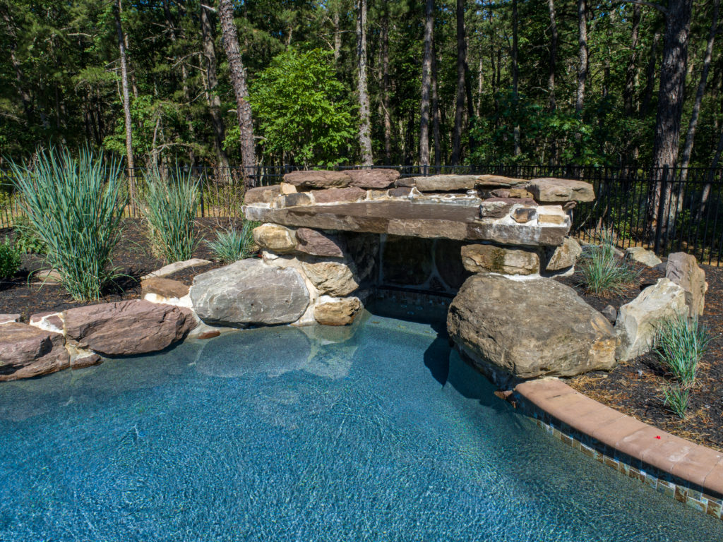 View of grotto feature in pool made of stone.