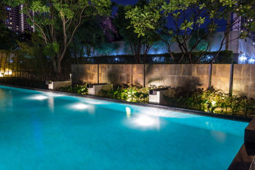 Pool surrounded by green plants illuminated for a relaxing evening.