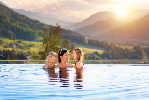 Mother and kids play in outdoor infinity swimming pool