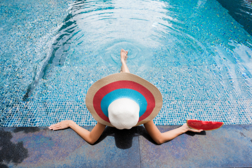 Woman with a white, blue and red sombrero relaxes as she puts her legs into a pool with a shimmering tile interior.