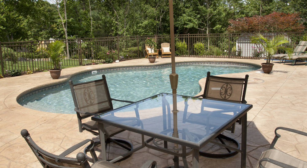 A view of an inground pool in a residential backyard pictured behind patio furniture.