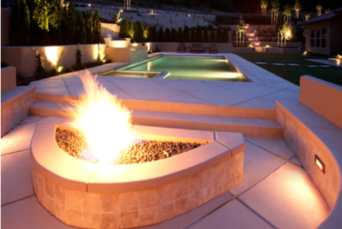 Small, rectangle in-ground luxury pool with an adjacent lit fire pit.