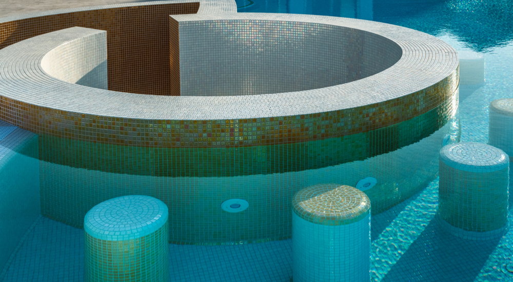 Pool with mosaic tile built-in bar stools featuring a partially underground pool bar.