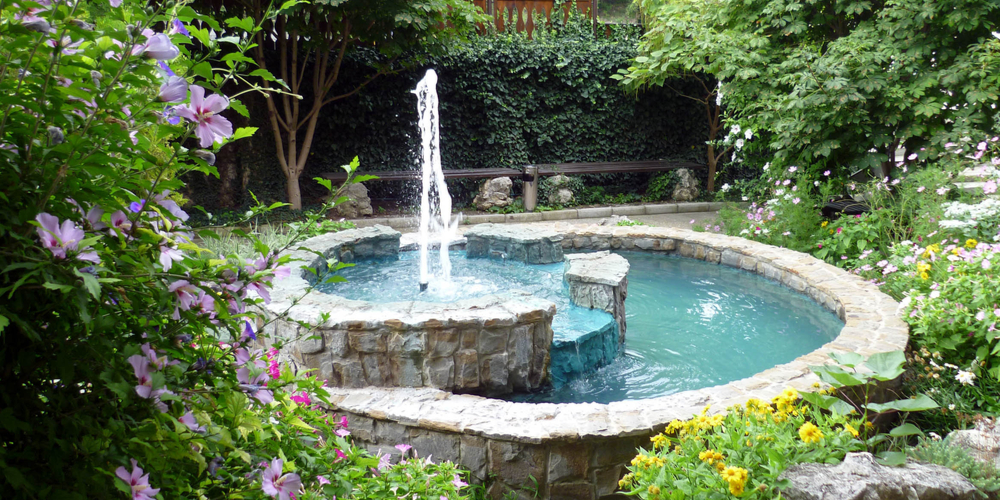 Beautiful stone fountain in the midst of a green garden.