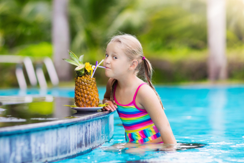 Child drinking juice in swimming pool bar.