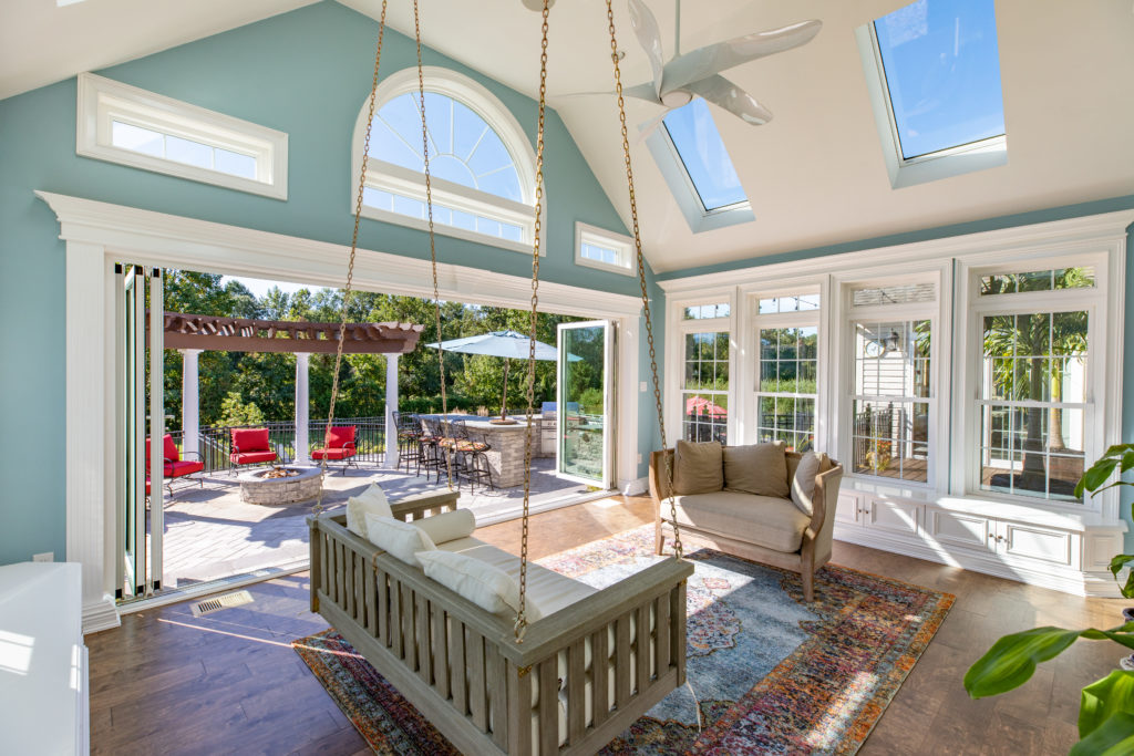 Beautiful family room open to the outdoors with high ceilings,multiple windows, and a couch hanging from a chain.