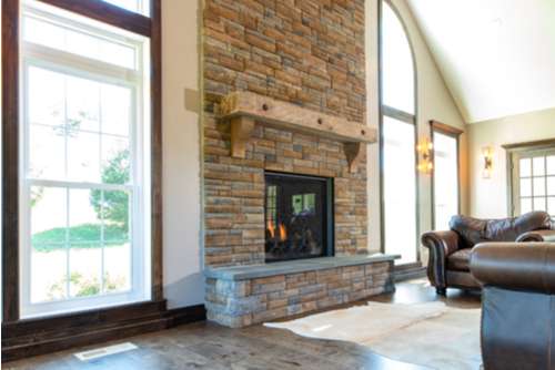 Gorgeous, tall, brick fireplace with wooden mantelpiece