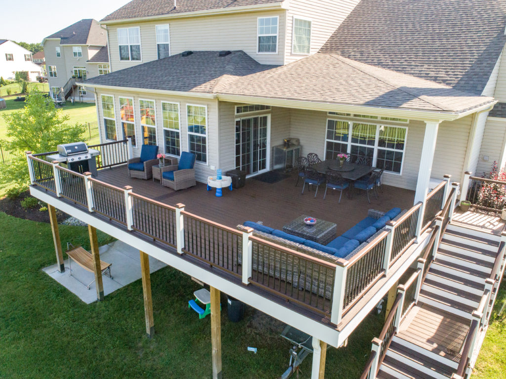 Raised, attached deck featuring blue furniture, a grill, and a dining table.