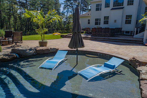 Two blue lounge chairs set in a sun shelf pool area.