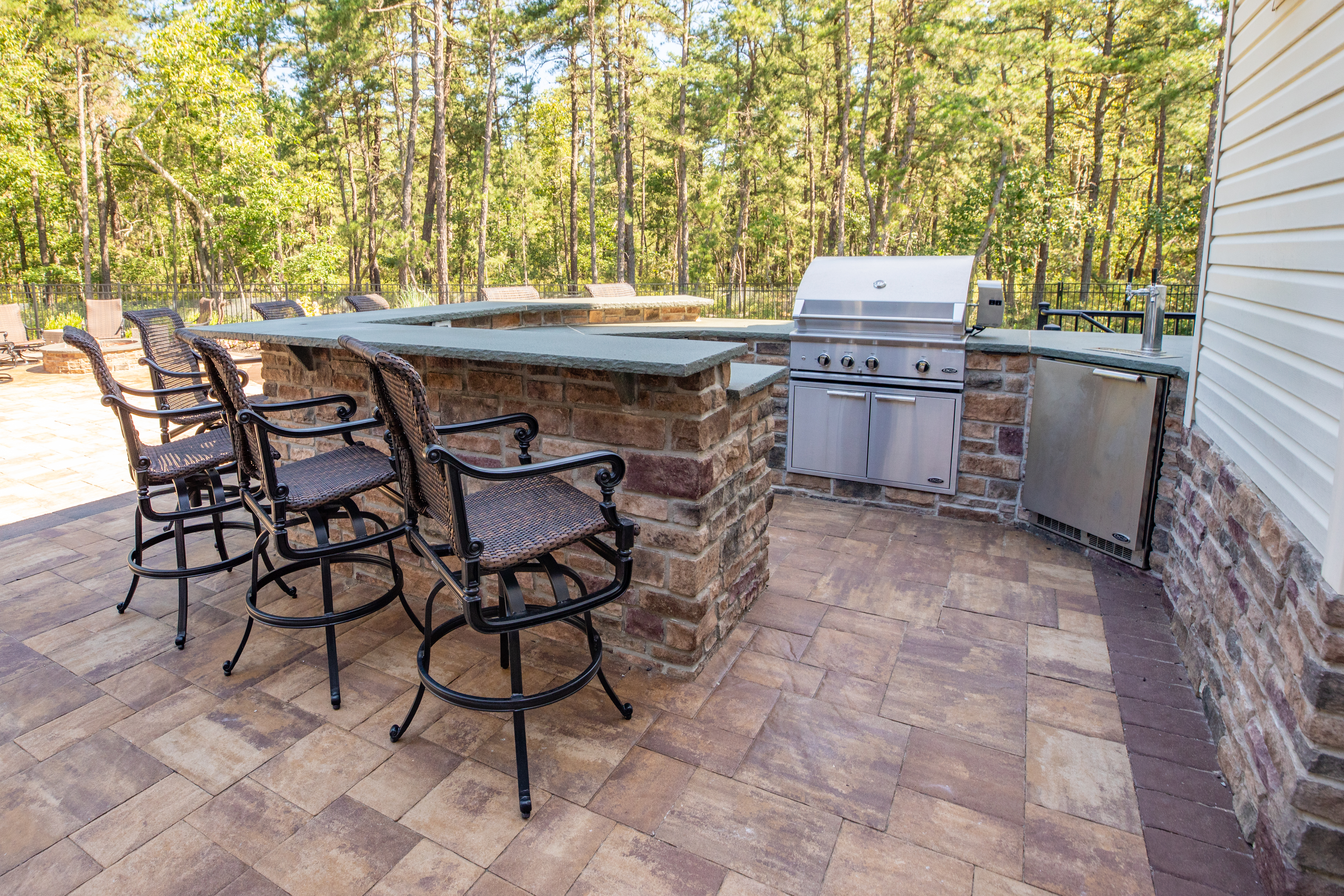 Outdoor kitchen featuring three bar stools, eating counter, stainless steel grill, and trees in the background.