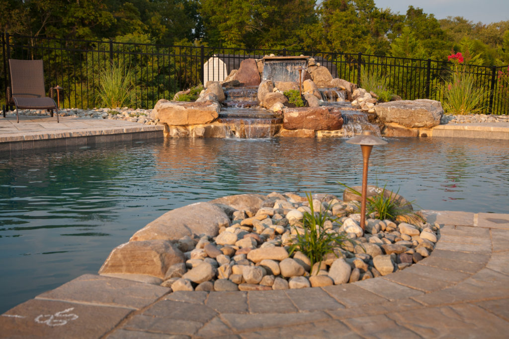 In ground pool with built-in rock waterfall.