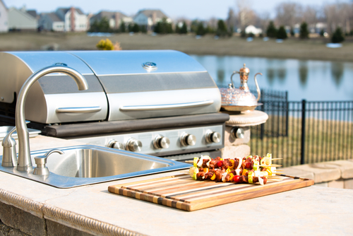 Closeup of stainless steel grill next to an outdoor sink and counter with a cutting board and kabobs, featuring a waterway.