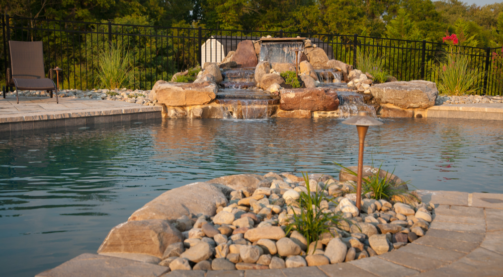 A natural-style waterfall adds extra pop to an outdoor pool area.