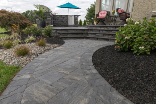 Gray paver pathway in backyard leading to deck.