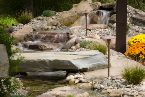 Waterfall flowing over stones in a backyard with a large, stone walkway featuring small light structures.